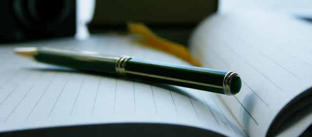 胸ポケットから万年筆を取り出す仕草
