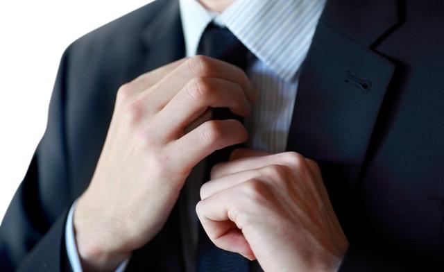 ネクタイをいじるしぐさ