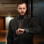 Handsome well-dressed man with beard looking at his wrist watch in a hallway